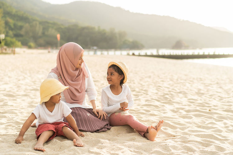 Mother wearing hijab with children sitting on sand at beach