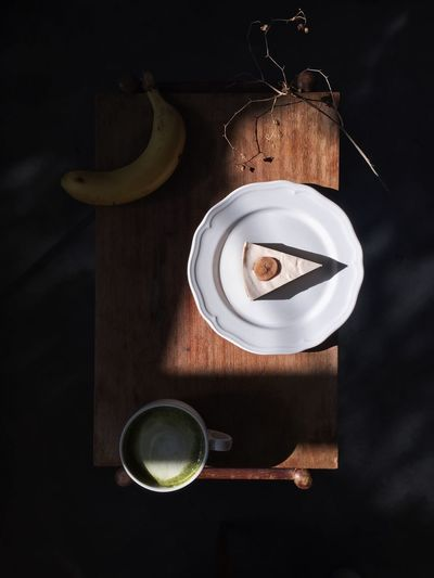 Directly above view of fresh cake slice served with banana and matcha tea on table