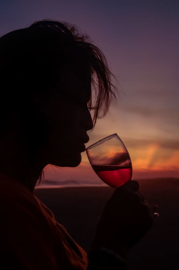 Close-up of woman drinking against sky during sunset