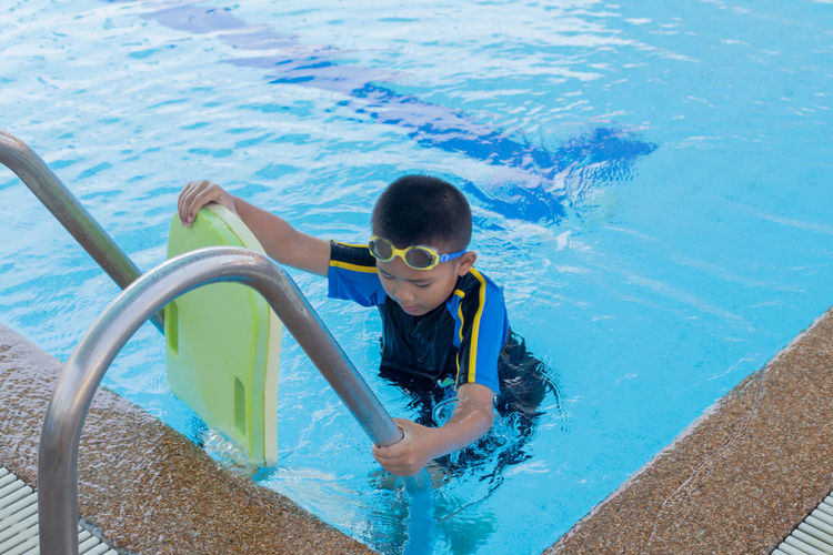 Boy with inflatable in swimming pool