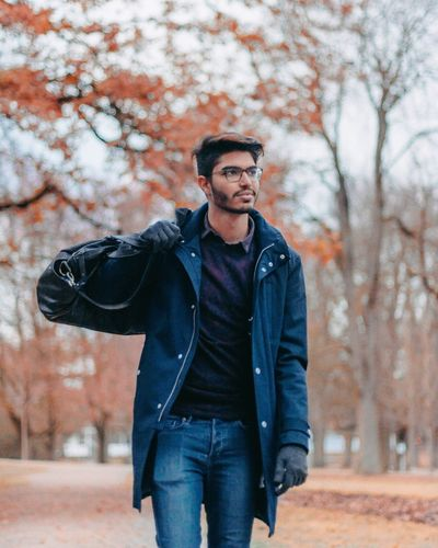 Young man walking with luggage in park during autumn