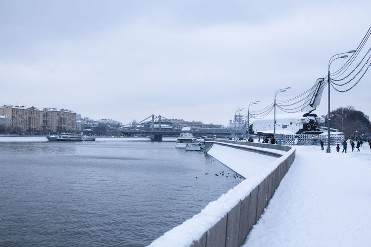Bridge over river in city against sky during winter