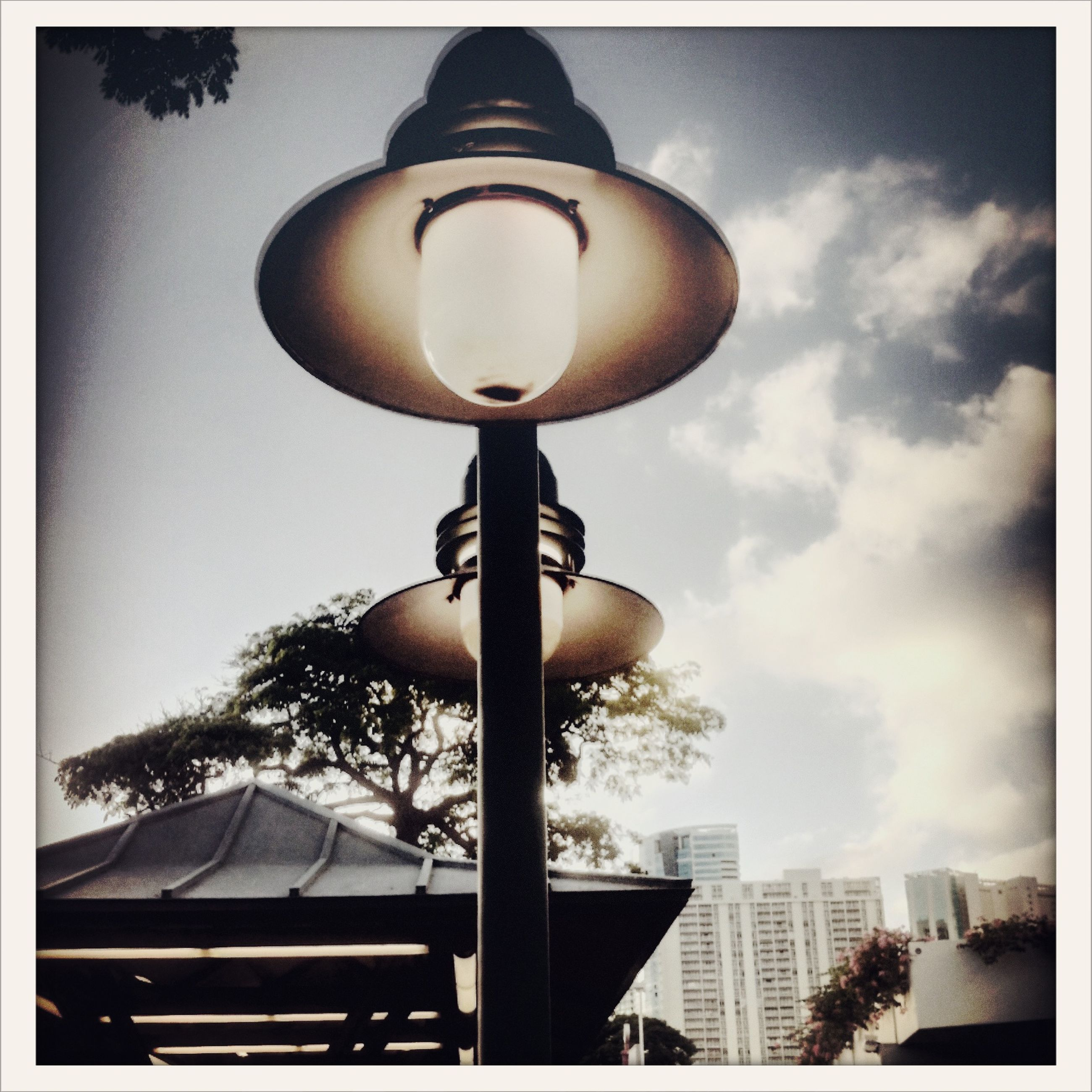low angle view, lighting equipment, transfer print, sky, street light, auto post production filter, illuminated, tree, built structure, electric lamp, electricity, cloud - sky, architecture, no people, electric light, technology, building exterior, hanging, day, sphere