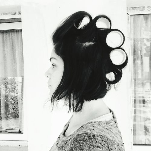 Side view of woman with hair curler at home