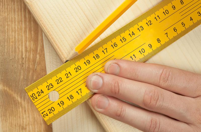 Close-Up Of Carpenter Taking Measurement Of Wood