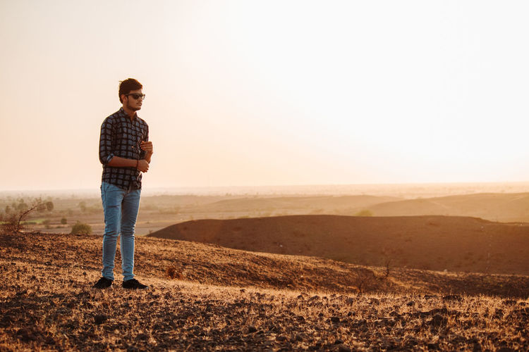 One Person Sky Landscape Land Full Length Copy Space Nature Casual Clothing Environment Tranquil Scene Scenics - Nature Tranquility Rural Scene Non-urban Scene Standing Field Adult Young Adult Outdoors Jeans Contemplation Looking At View