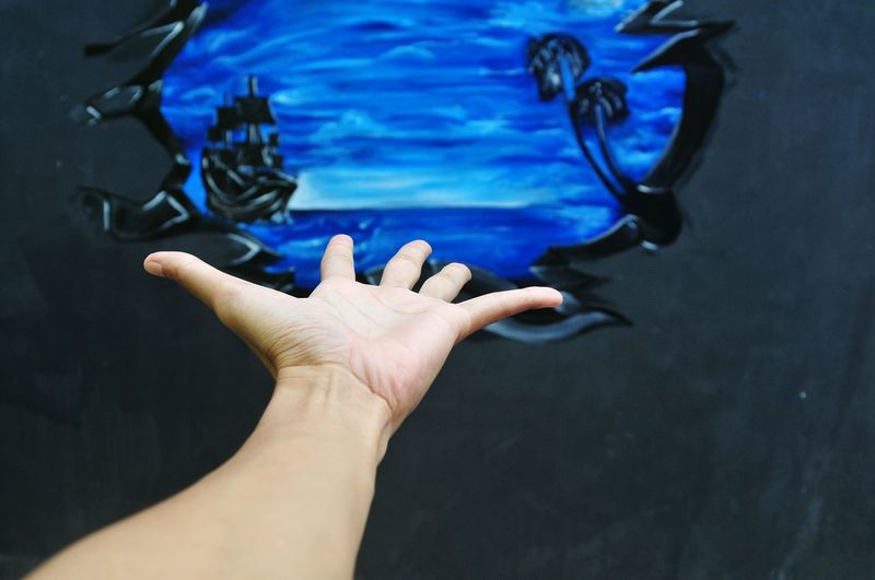 Cropped Image Of Hand Gesturing Towards Graffiti Wall