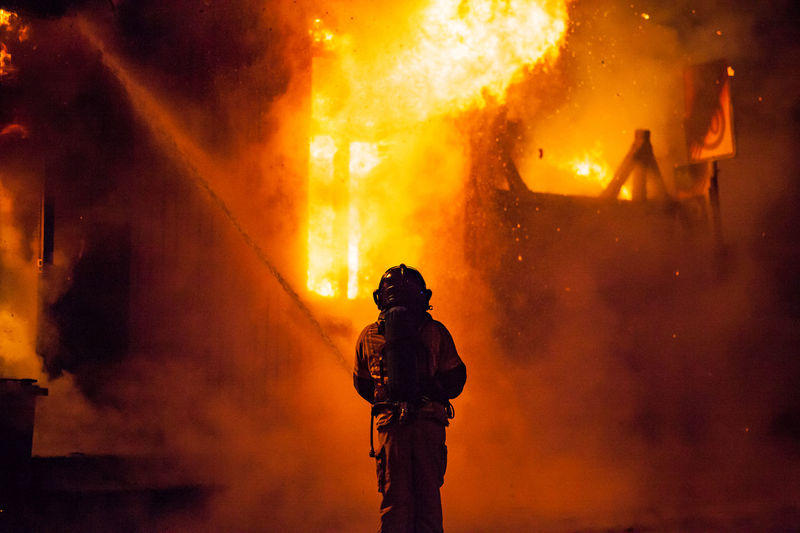 Rear View Of Firefighter At Night