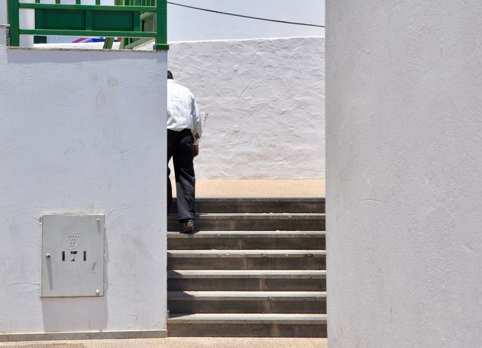 Rear view of man on staircase against wall