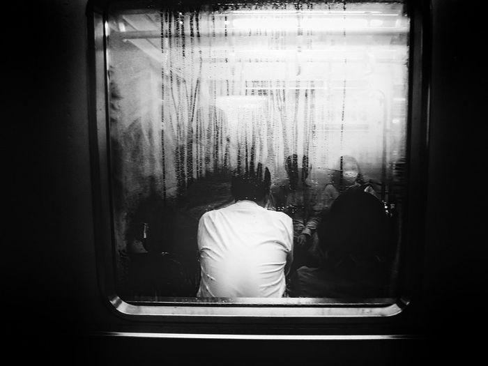 Rear view of people looking through train window