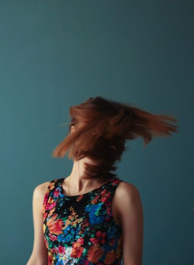 Redhead woman tossing hair against blue background