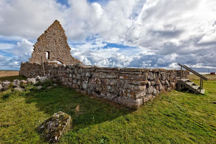 Historic Old Ruins Of Saint Birgitta Chapel On Grass Against Sky
