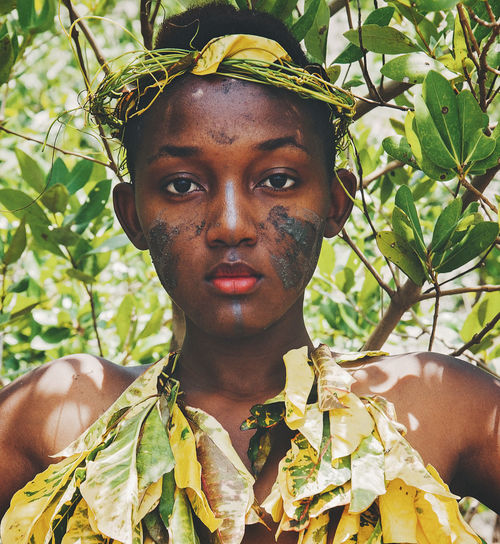 Close-Up Portrait Of Female Model Wearing Leaves By Plants