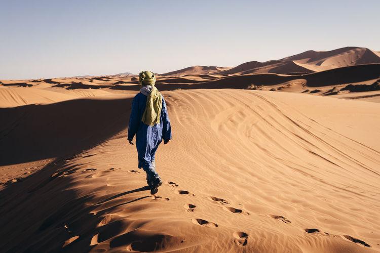 Rear view of man walking on desert