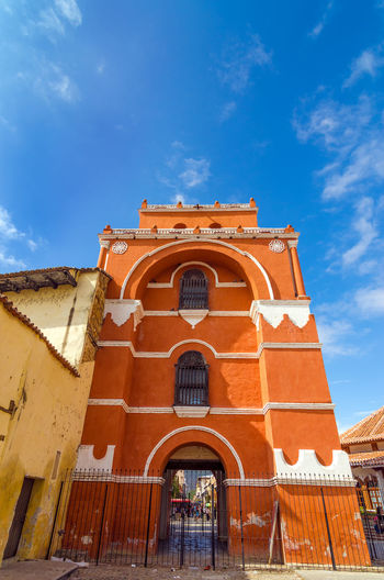 Low angle view of arco torre del carmen against blue sky