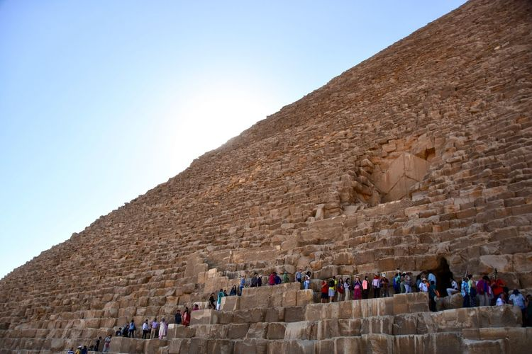 Low angle view of tourists in front of great pyramids
