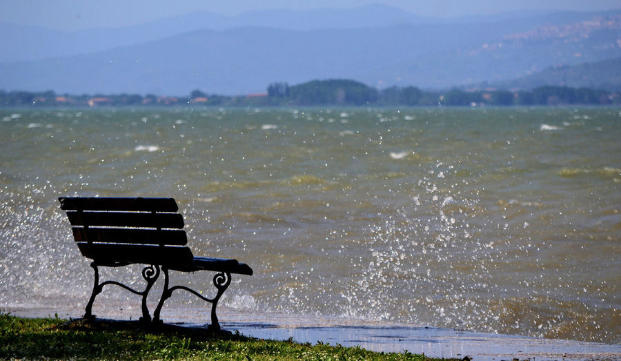 bench along the shoreline of a lake on a windy day Park Bench Outdoors Grass Outdoor Chair Absence Nature Bench Seat Water Scenics - Nature Beauty In Nature Empty Lake Lake View Wave Wind
