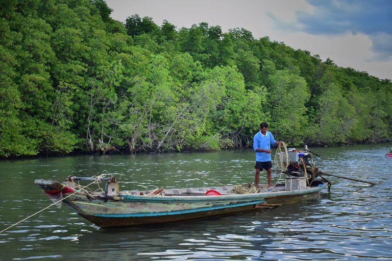 Men standing on boat in lake against trees