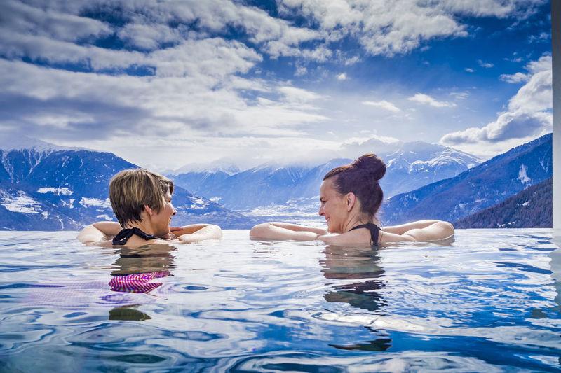 Friends in swimming in sea against sky