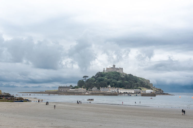 the lesser known counterpart to the french island is St Michaels Mount in Cornwall. At low tide you can walk there, which lots of tourists happily do. Castle Architecture Beach Beauty In Nature Building Built Structure Cloud - Sky Day Incidental People Island Land Low Tide Nature Nautical Vessel Outdoors Sand Scenics - Nature Sea Sky Travel Travel Destinations Water