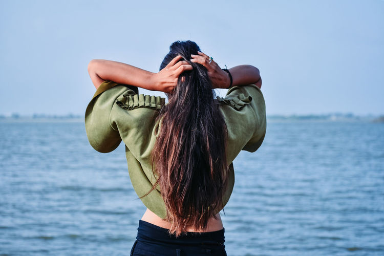 Rear view of woman tying hair standing by sea against sky