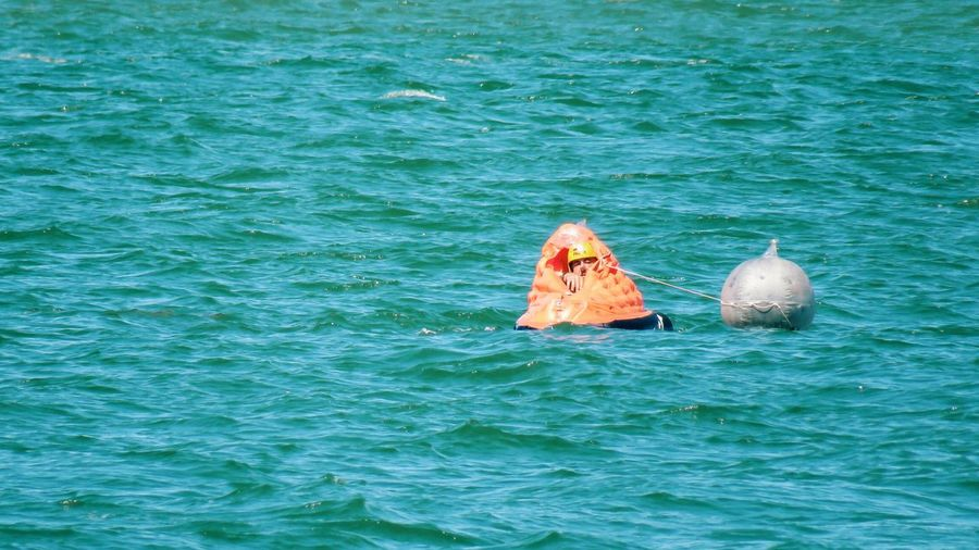 Man in lifeboat floating on turquoise sea