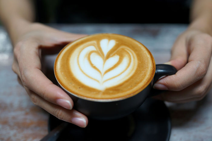 Close up female hand holding a cup of latte Cafe Close-up Coffee Coffee - Drink Coffee Cup Cup Drink Finger Food And Drink Froth Art Frothy Drink Hand Holding Hot Drink Human Body Part Human Hand Latte Mug One Person Real People Refreshment