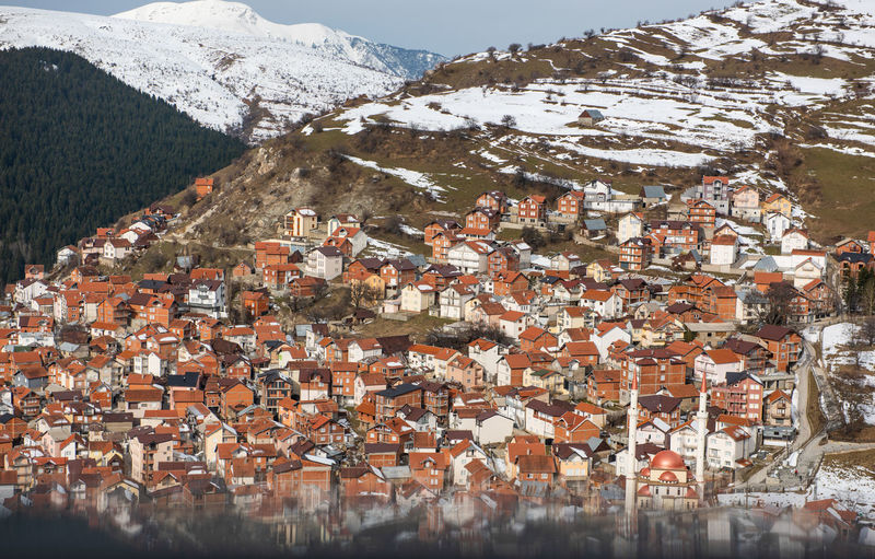 Aerial view of townscape against snowcapped mountain
