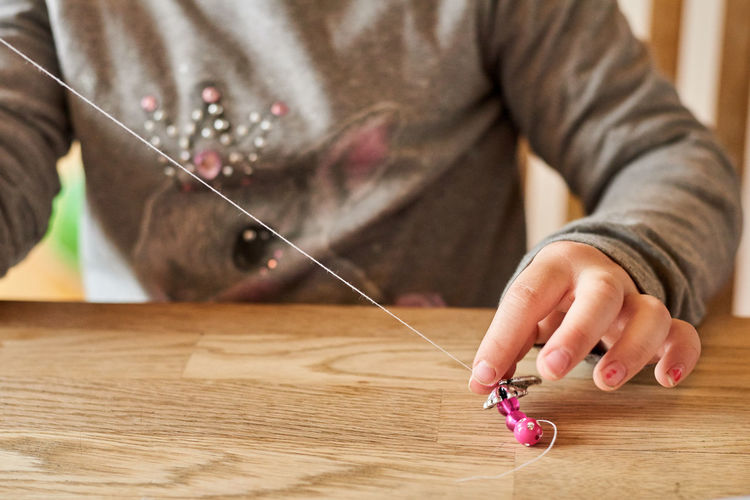Midsection of girl making jewelry on table