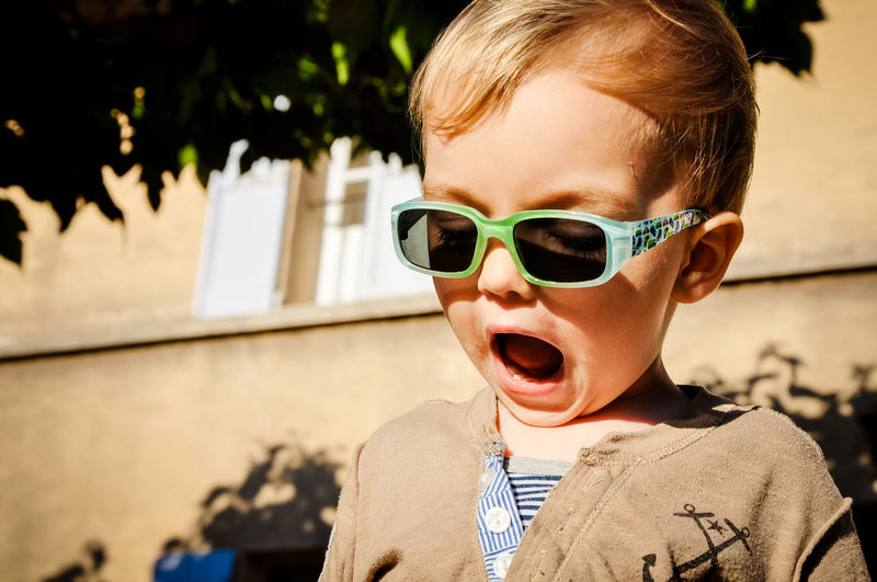 Close-up of cute boy in sunglasses with open mouth outdoors