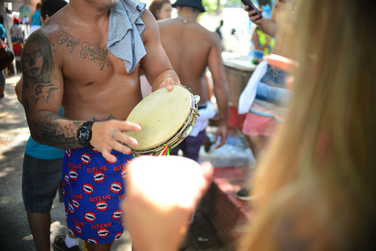 Midsection of shirtless man playing drum outdoors