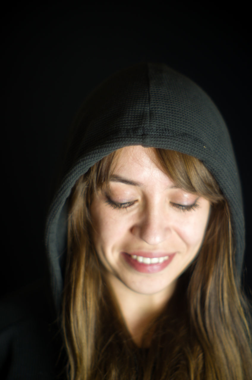 Close-Up Of Smiling Young Woman Against Black Background