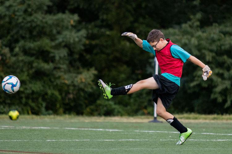 Full length of boy kicking soccer ball on grass in a game