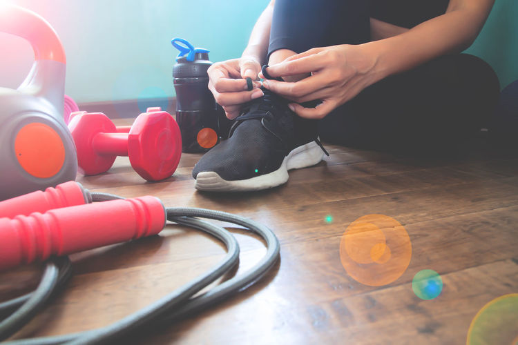 Fitness woman tying shoes, Workout at home Beautiful Lifestyle Sport Shoes Tying Woman Adult Beauty Dumbbell Equipment Fitness Flooring Health Healthy Human Body Part Human Hand Jumping Rope Kettlebell  Lifestyles One Person Real People Sitting Sneakers Sport Wood