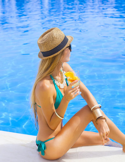 Young woman wearing hat while sitting on swimming pool
