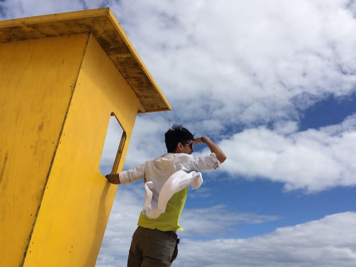 Low Angle View Of Man On Yellow Lifeguard Hut Against Cloudy Sky