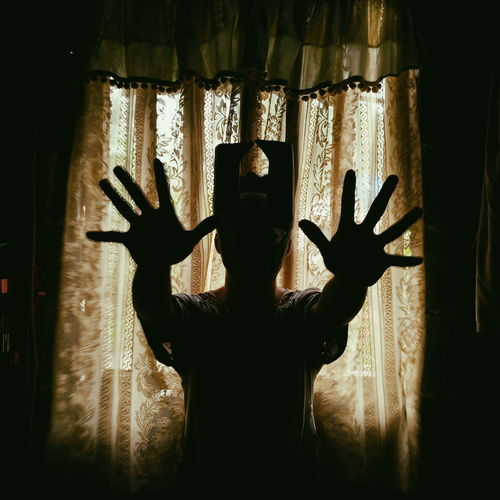 Silhouette man gesturing while standing by curtain