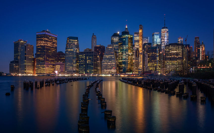New York city skyline Reinaroundtheglobe Building Exterior Architecture Built Structure Water Building City Reflection Office Building Exterior Illuminated Skyscraper Sky Waterfront Cityscape Urban Skyline Tall - High Landscape No People Financial District  New York Manhattan Blue Hour Long Exposure