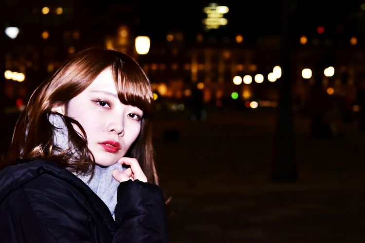 Portrait of beautiful woman in city at night