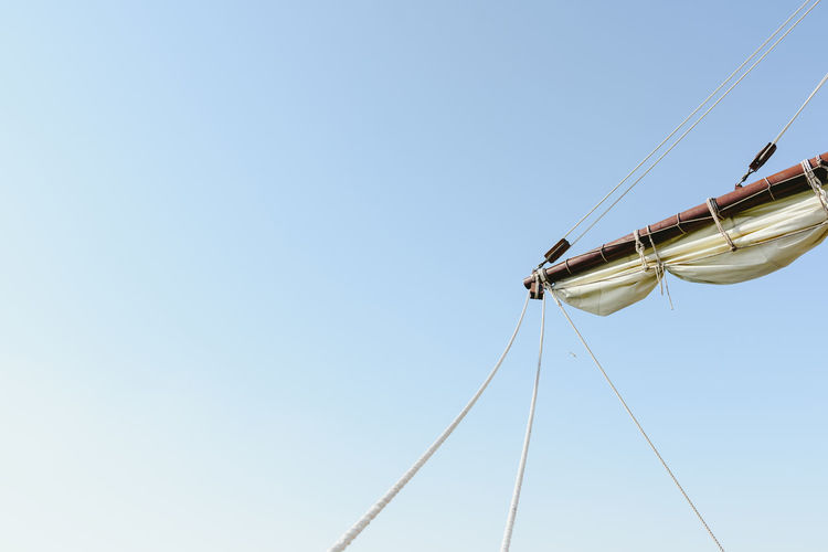Low angle view of sailboat against clear sky