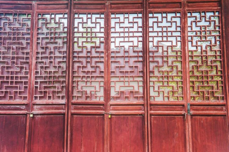 Chinese traditional door Carved Wooden Door Traditional Door Traditional Window Wooden Door Wooden Window Chinese Full Frame Wood - Material Red Brick Wall Architecture Built Structure Close-up Wooden Closed Door Entryway Front Door Wall Door Peeling Off