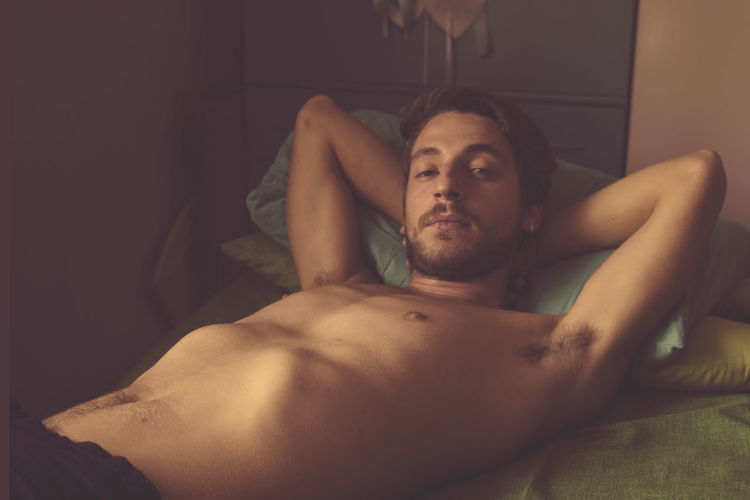 Portrait Of Shirtless Man Lying In Bed