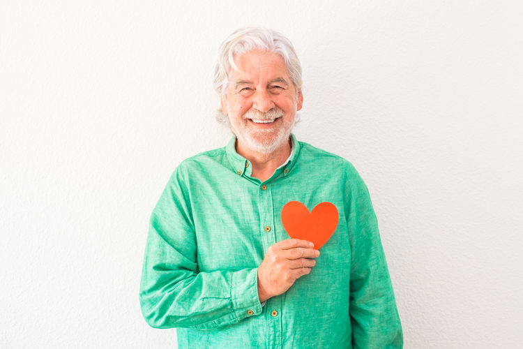 Portrait of smiling man holding heart shape over white background
