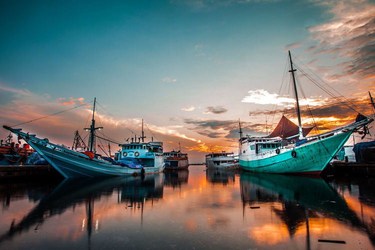 Landscape at Paotere Makassar, fishing boats from Pangkep islands break while waiting for cargo of goods to be brought back to the island Harbor Water Pier Moored Night Travel Destinations Sky Sea Outdoors Ship Commercial Dock No People Beach Blue Vacations Sunset