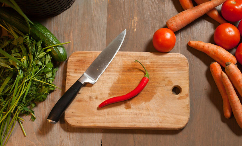 High angle view of vegetables with cutting board on wooden table