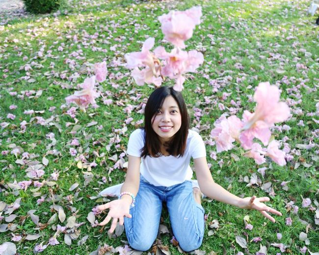 Portrait of smiling young woman sitting on pink flowering plants