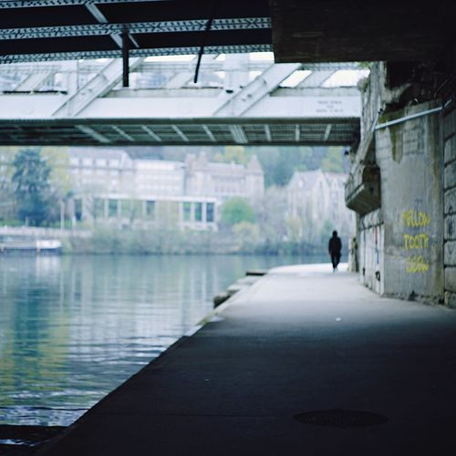 Rear View Walking Built Structure Architecture One Person Water Urban Landscape Under The Bridge Along The Riverside Eerie Ominous Square Format Lovers 50mm Leica Lens Lyon Saône River Street Photography Urban Exploration