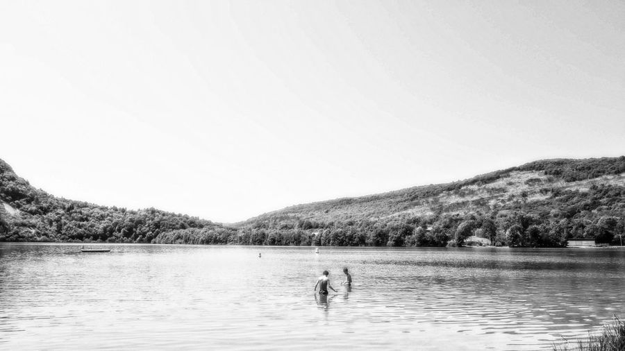 Black & White Riverside Beauty In Nature Blackandwhite Blackandwhite Photography Lake Leisure Activity Men Mountain Nature Sky Swimming Two People Water