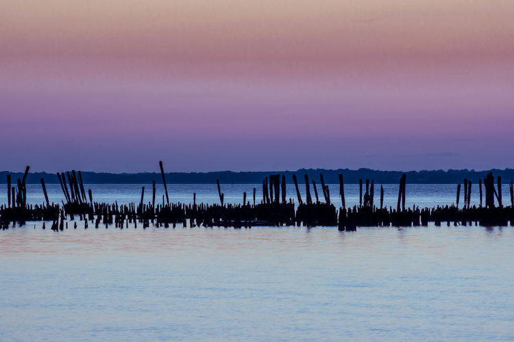 Silhouette Wooden Post In Seascape During Sunset