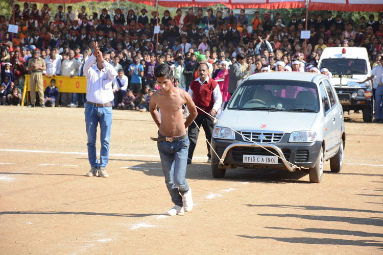 EyeEmNewHere Superhuman Powerful Car Pulling Out Shoulder Blade Kid Little Hero Stadium Audience Entertainment Event Outdoors Shirtless Strongman Amazing Unbelievable Crowd Large Group Of People